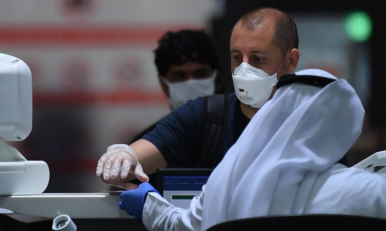 دبئی کے انٹر نیشنل ایئرپورٹ پر ایک مسافر اپنی سفری دستاویزات کی جانچ کروا رہا ہے — فوٹو: اے ایف پی