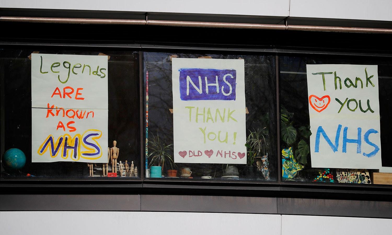 لندن میں سینٹ تھامس ہسپتال کے سامنے ایک کالج کی کھڑکیوں سے صحت حکام کو خراج تحسین پیش کرنے کے لیے آویزاں کیے گئے مختلف پیغامات نظر آرہے ہیں — فوٹو: اے ایف پی