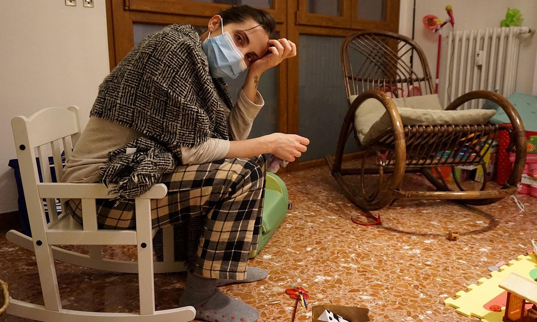 اٹلی میں ایک ڈاکٹر ہسپتال کے ایمرجنسی وارڈ میں طویل ڈیوٹی کرنے کے بعد اپنے گھر میں سر کو تھامے بیٹھی ہیں — فوٹو: رائٹرز