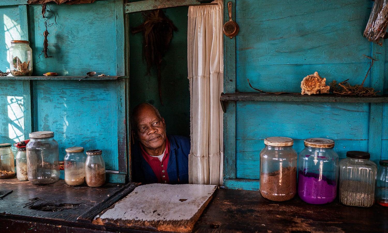 لاک ڈاؤن کے باعث جنوبی افریقہ میں ایک حکیم اپنے گاہکوں کا منتظر ہے — فوٹو: اے پی