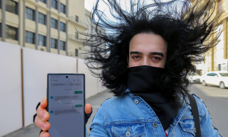 آذربائیجان میں ایک شخص موبائل پر وہ پیغام دکھا رہا ہے جس کے تحت اسے گھر سے باہر نکلنے کی اجازت دی گئی — فوٹو: رائٹرز