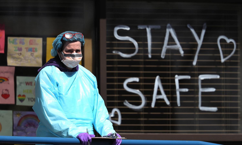 امریکا میں کورونا وائرس سے سب سے زیادہ متاثر ہونے والی ریاست نیویارک میں ایک صحت کی رضاکار وائرس کی ٹیسٹنگ سائٹ کے پاس موجود ہے — فوٹو: اے ایف پی