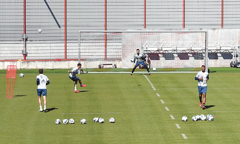 MUNICH: Bayern Munich players try to keep a safe distance during their training session on Monday.—Reuters