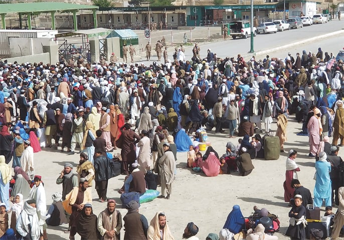 CHAMAN: People gather as they wait to cross the Friendship Gate crossing point at Pakistan-Afghanistan border on Monday.—Reuters