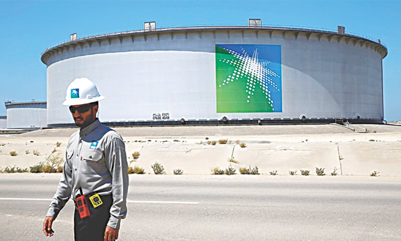An Aramco employee walks near an oil tank at Saudi Aramco's Ras Tanura oil refinery. Sources say Moscow is ready for a significant oil output reduction provided other producers would do the same while Riyadh insists it will no longer carry what it considers an unfair burden of cuts.—File photo