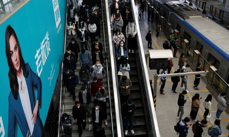 People wearing face masks are seen inside a subway station during morning rush hour in Beijing, as the spread of Covid-19 continues in the country. — Reuters