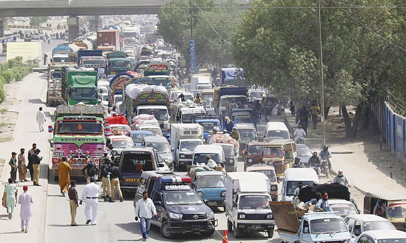 Security officials inspect passengers and vehicles at Sohrab Goth on Tuesday as part of the government's measures to prevent the spread of the coronavirus in Sindh.—PPI
