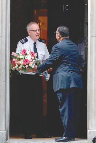LONDON: An official of the Pakistan High Commission delivers flowers to No 10, Downing Street, the residence of Prime Minister Boris Johnson.—AFP