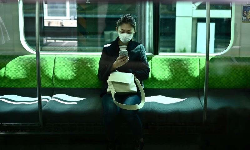 A woman uses her phone on the Yamanote Line train in Tokyo on April 8, on the first day of the state of emergency. — AFP