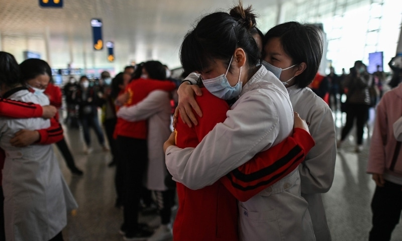 Medical staff from Jilin Province (in red) hug nurses from Wuhan after working together during the coronavirus outbreak during a ceremony before leaving as Tianhe Airport is reopened in China's central Hubei province on April 8. — AFP/File