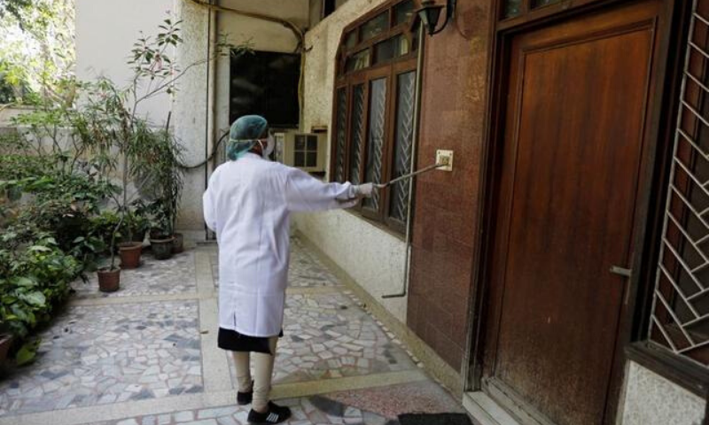 A doctor uses a piece of wood to press a door bell switch during a door-to-door verification of residents to find out if they have developed any coronavirus symptoms, in Nizaumuddin area of New Delhi, India. — Reuters