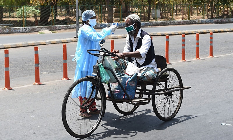 A health worker checks the body temperature of a man with mobility impairment in Ahmedabad on April 8. — AFP