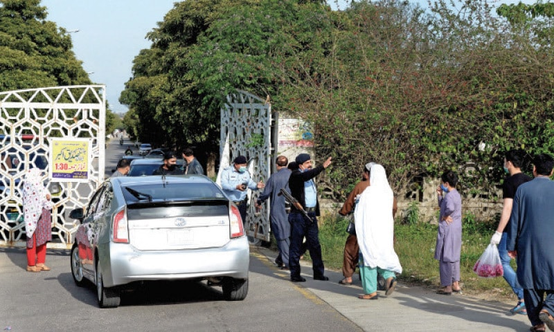 Police personnel stop people from visiting the H-11 graveyard in Islamabad on the occasion of Shab-i-Barat on Wednesday. — Photo by Mohammad Asim