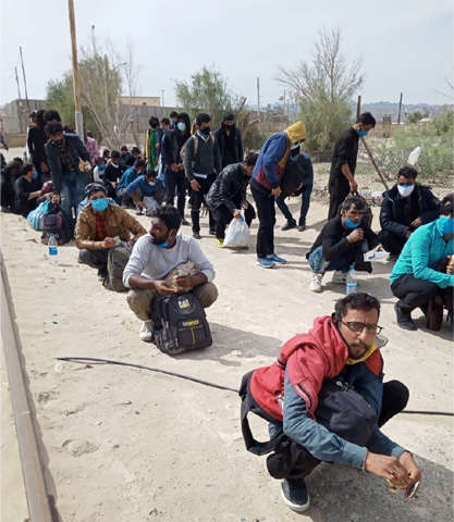 TAFTAN: Pakistani citizens wait at Raahdari Gate to get screened by health teams after being deported from Iran for not having legal travelling documents.—Dawn