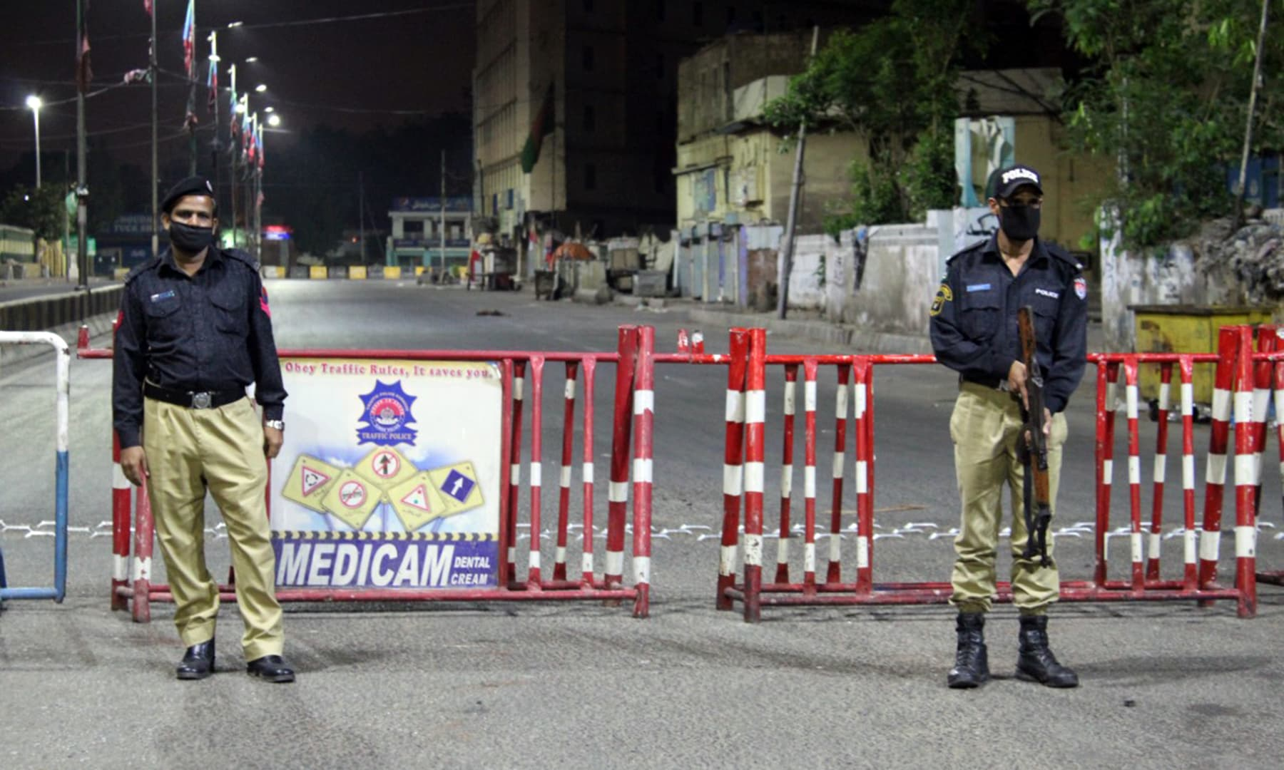 Policemen stand at a blocked street during the lockdown in Karachi.