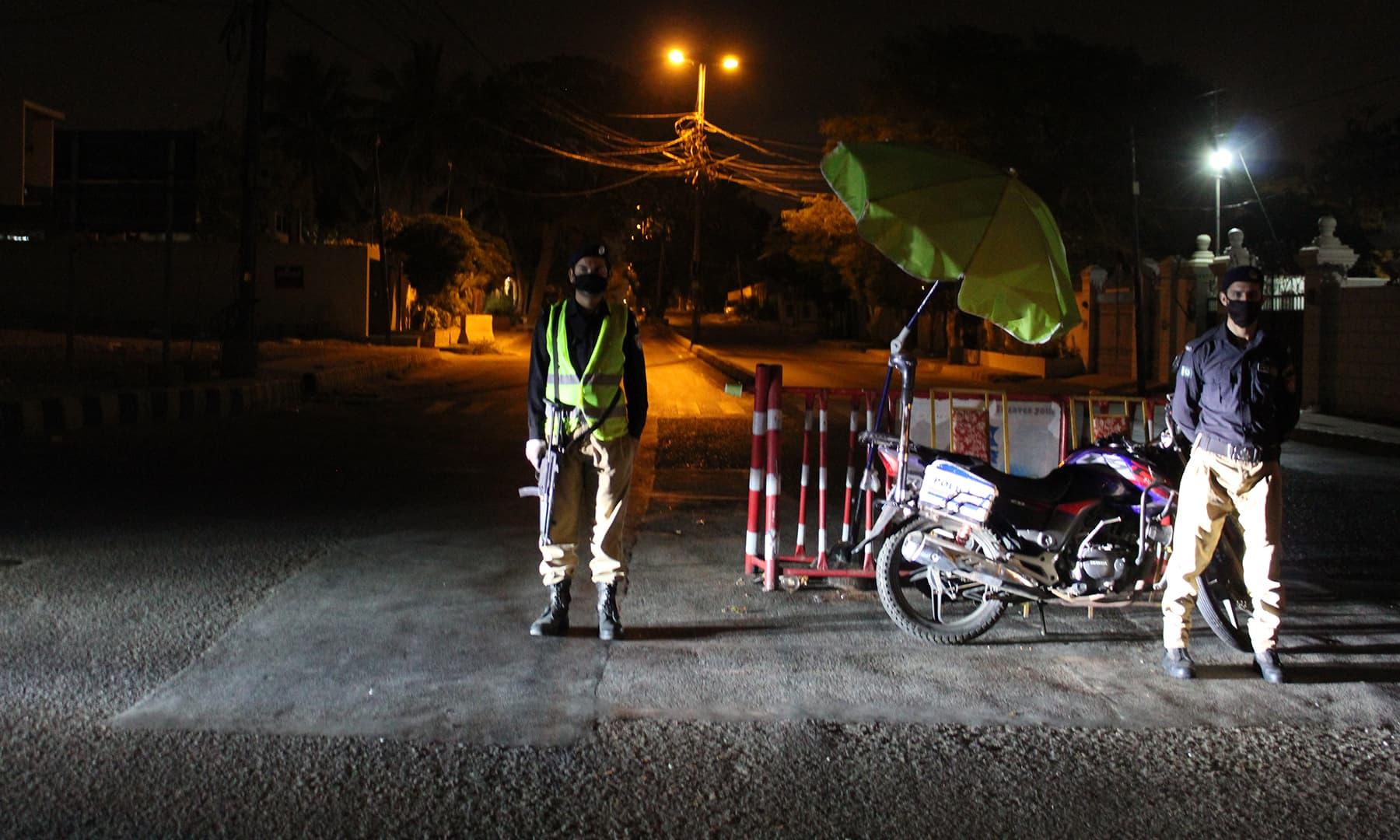 Policemen wearing masks stand guard at an empty street in Karachi.