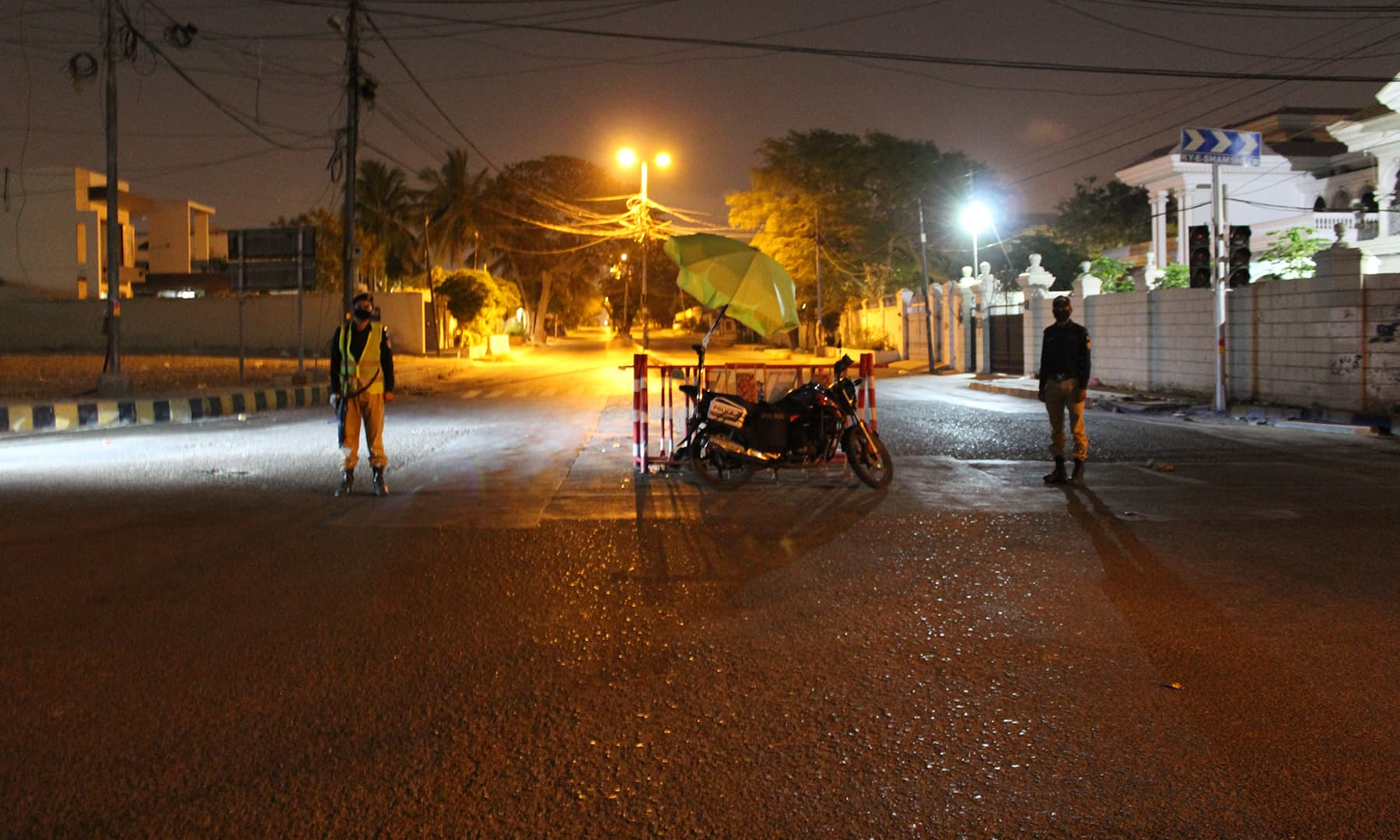 Police personnel perform duty at a street in Karachi's DHA.
