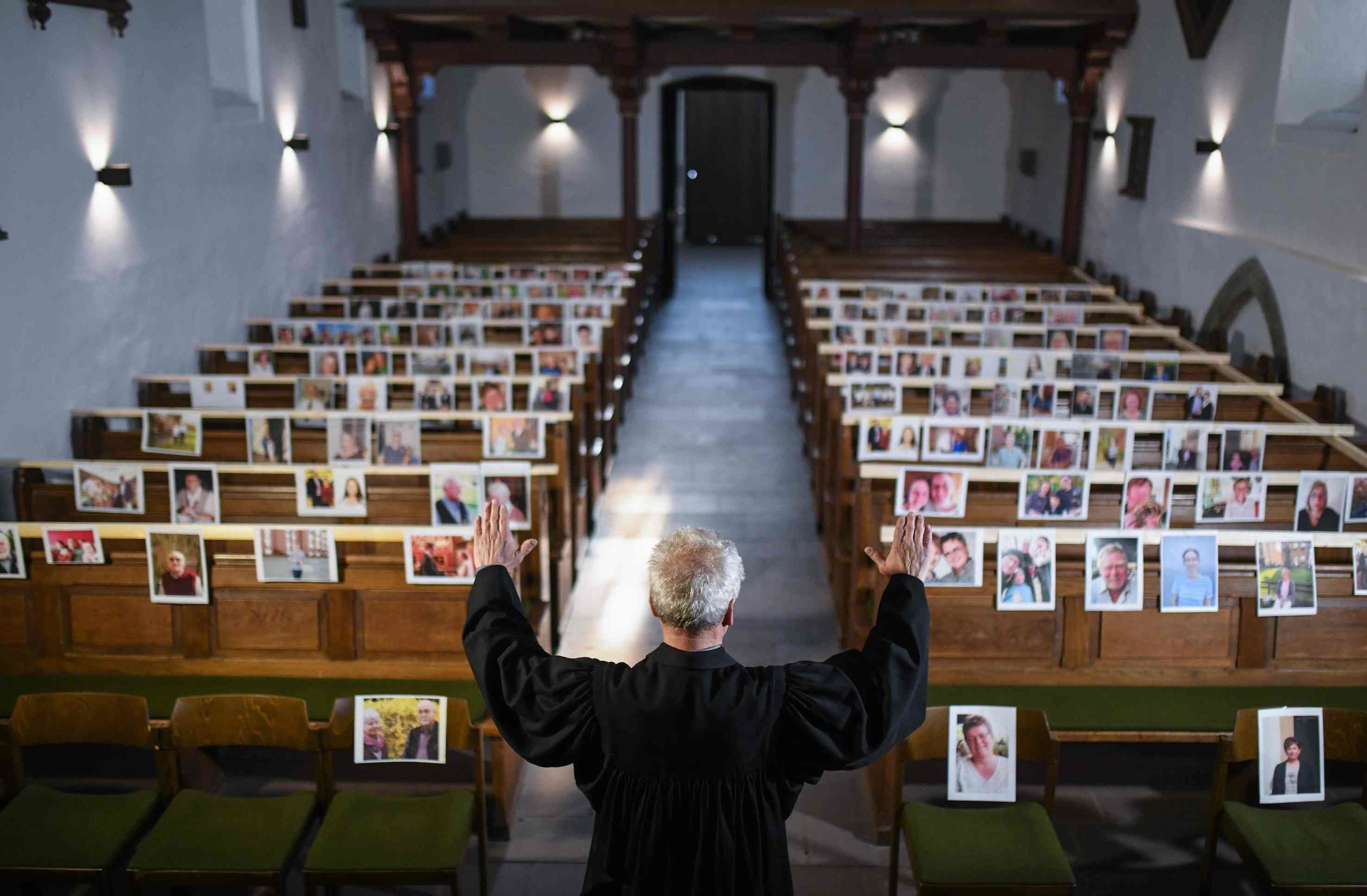 The evangelical pastor Klaus-Martin Pothmann stands in front of photos of believers who were asked to send in pictures to represent them among the pews at the St. Pankratius church in Hamm, western Germany, on April 9, 2020, due to the spread of the novel coronavirus COVID-19. — AFP
