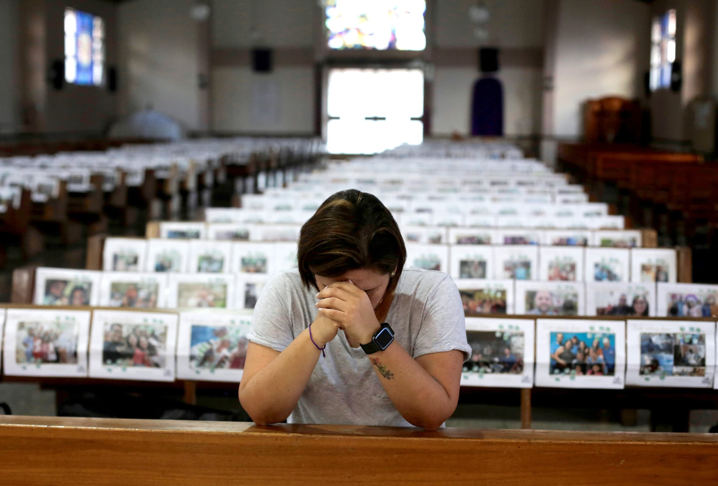 Catholic Adriana Brenes prays during a live streamed mass as photos of the faithful are displayed over the church's benches at the Nuestra Senora de Fatima church, as the spread of the coronavirus disease (COVID-19) continues, in San Jose, Costa Rica April 8, 2020. — Reuters