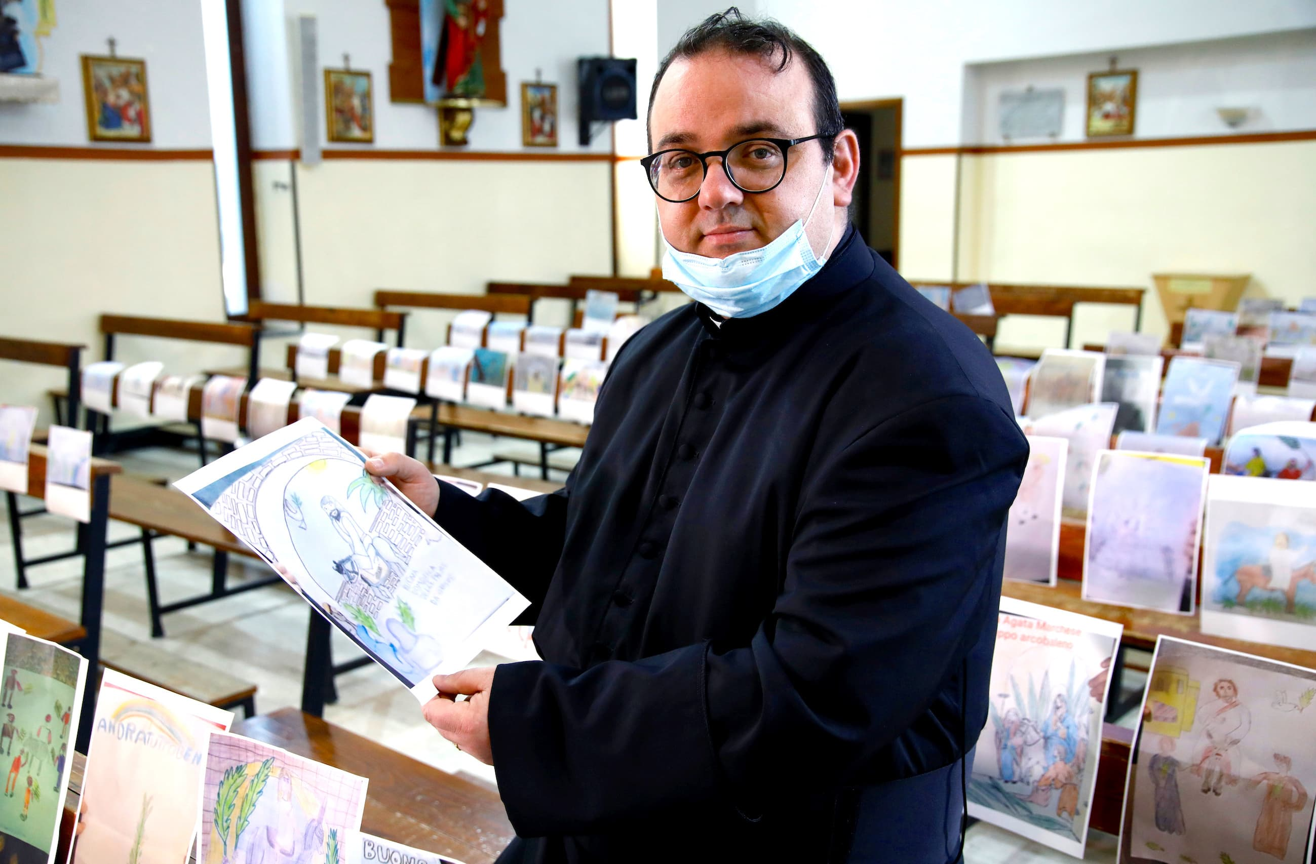 Father Fabio Vassallo poses with drawings done by children of members of the congregation decorating the pews, ahead of a Holy Thursday Mass in an empty church, as Italy celebrates Easter under lockdown. — Reuters