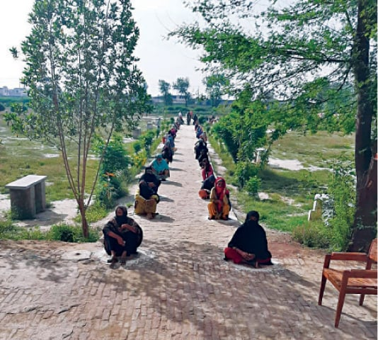 FAISALABAD: Women sit on ground prior to getting financial assistance. — Dawn