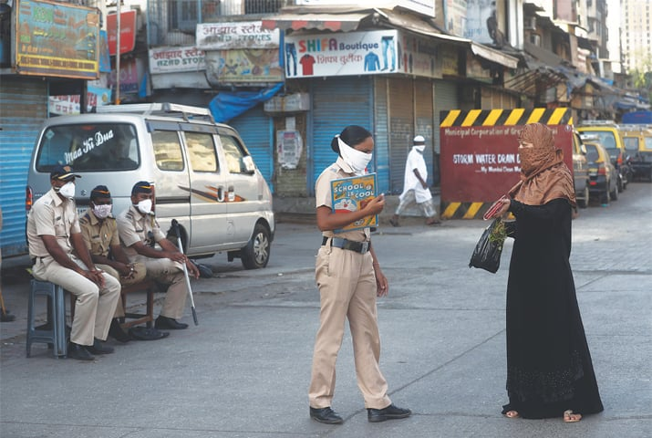 An Indian police officer stops a woman in Mumbai's Dharavi, one of Asia's largest slums, during lockdown to prevent the spread of the coronavirus.—AP