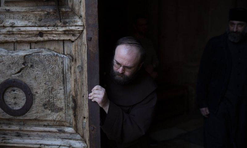 A priest closes the door of the Church of the Holy Sepulchre, a place where Christians believe Jesus Christ was buried, during a lockdown following government measures to help stop the spread of the coronavirus, during Holy Thursday in Jerusalem's old city. — AP