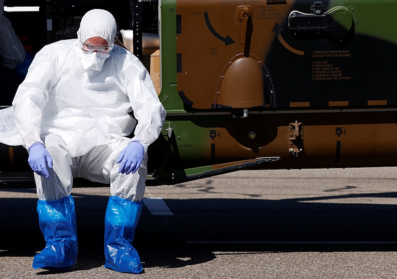 A health worker wearing a protective gear takes a break during transfer operations of patients infected with coronavirus disease from Strasbourg, France to Germany on March 30, 2020. Picture taken March 30, 2020.    — Reuters