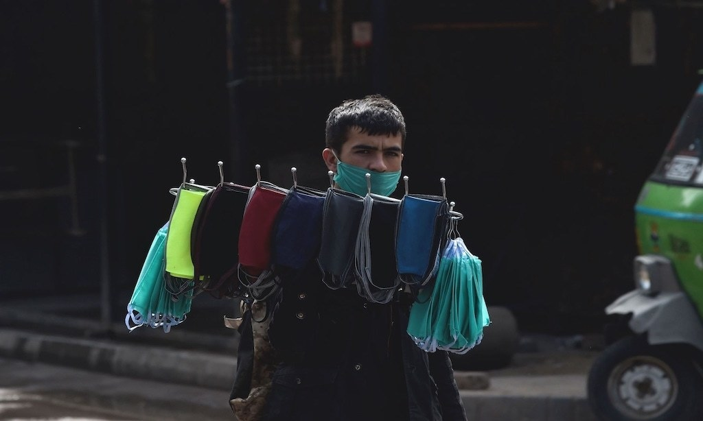 A vendor carries facemasks for sale | AFP