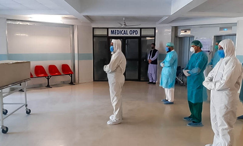 The three-member group along with health staff and doctors perform funeral prayers of a person who died from Covid-19 in Saidu Sharif Teaching Hospital in Mingora, Swat.