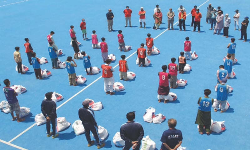 KARACHI: Former hockey Olympians led by ex-captain Islahuddin and Ayaz Mahmood distribute ration bags and other goods among the ground staff and sports persons during KSF welfare drive here at the Islahuddin-Dr Shah Academy on Saturday.