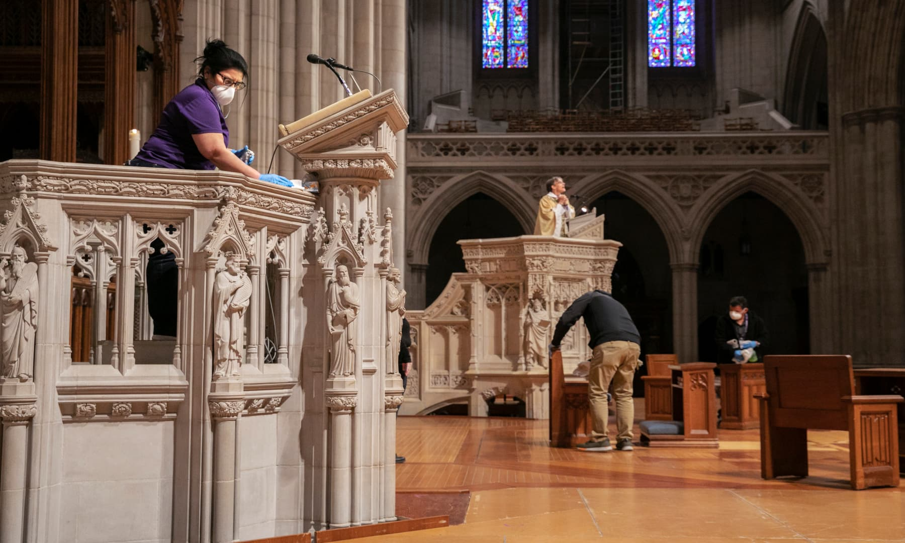 Wearing a face mask, Erlinda Ortega, top left, cleans a pulpit, while Bishop Mariann Edgar Budde, at centre, with the Episcopal Diocese of Washington, prepares to record a homily, after Budde led Easter Sunday services via livestream to an empty National Cathedral on April 12 in Washington, in light of coronavirus pandemic precautions. — AP