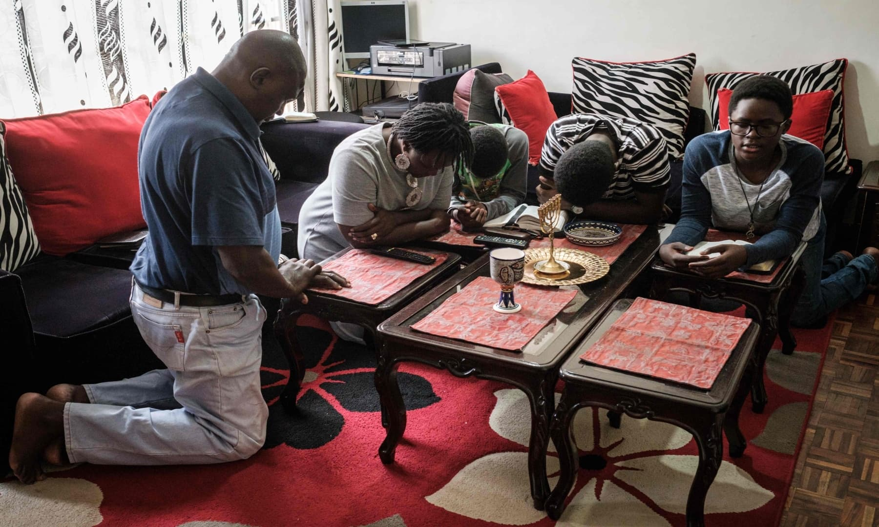 A Christian family prays together at home as they follow the live broadcasting of an Easter Sunday service on television from the All Saints' Cathedral in Nairobi, Kenya, on April 12. — AFP