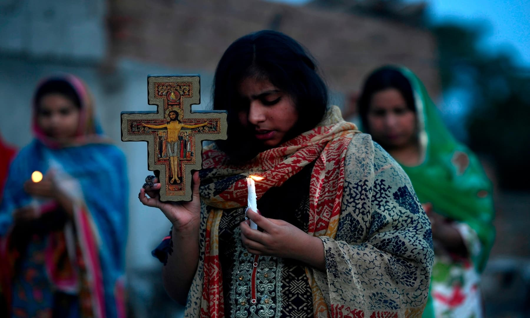 Christians hold candles as they offer prayers during an Easter service in the rooftop of their house in Islamabad. — AFP