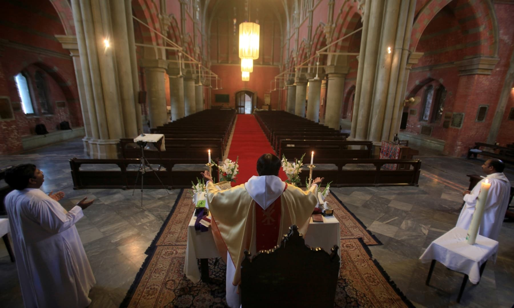 Reverend Shahid Mehraj Dean leads an online Easter prayer in front of empty seats at the Cathedral Church of the Resurrection in Lahore on April 12. — Reuters