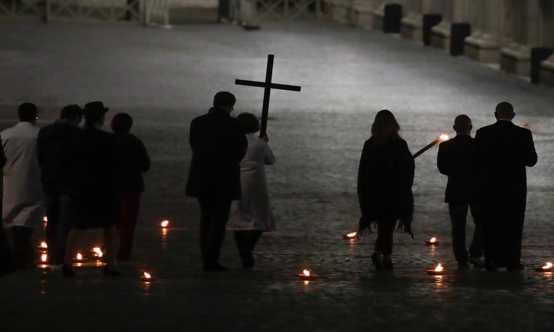 A woman holds the cross during the Via Crucis — or Way of the Cross — ceremony in St Peter's Square empty of the faithful following Italy's ban on gatherings to contain coronavirus contagion, at the Vatican on April 10. — AP