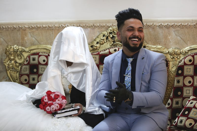 In this Thursday, April 9, 2020 photo, Ahmed Khaled al-Kaabi and his bride Ruqaya Rahim sit during their wedding in Najaf, Iraq, the hardest hit town by coronavirus in the country. — AP