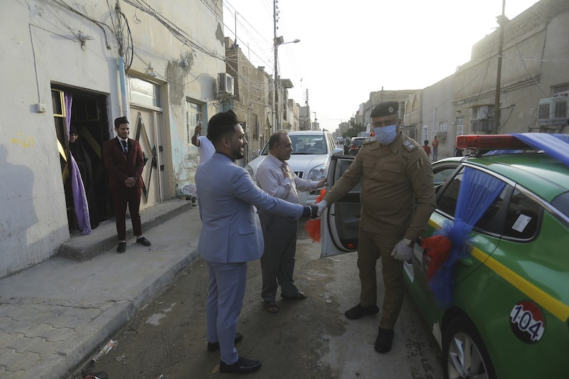 Police officers arrive to escort Ahmed Khaled al-Kaabi and his bride Ruqaya Rahim during their wedding in Najaf, Iraq. — AP