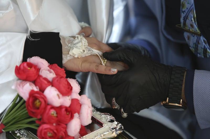 Ahmed Khaled al-Kaabi and his bride Ruqaya Rahim hold hands during their wedding. — AP