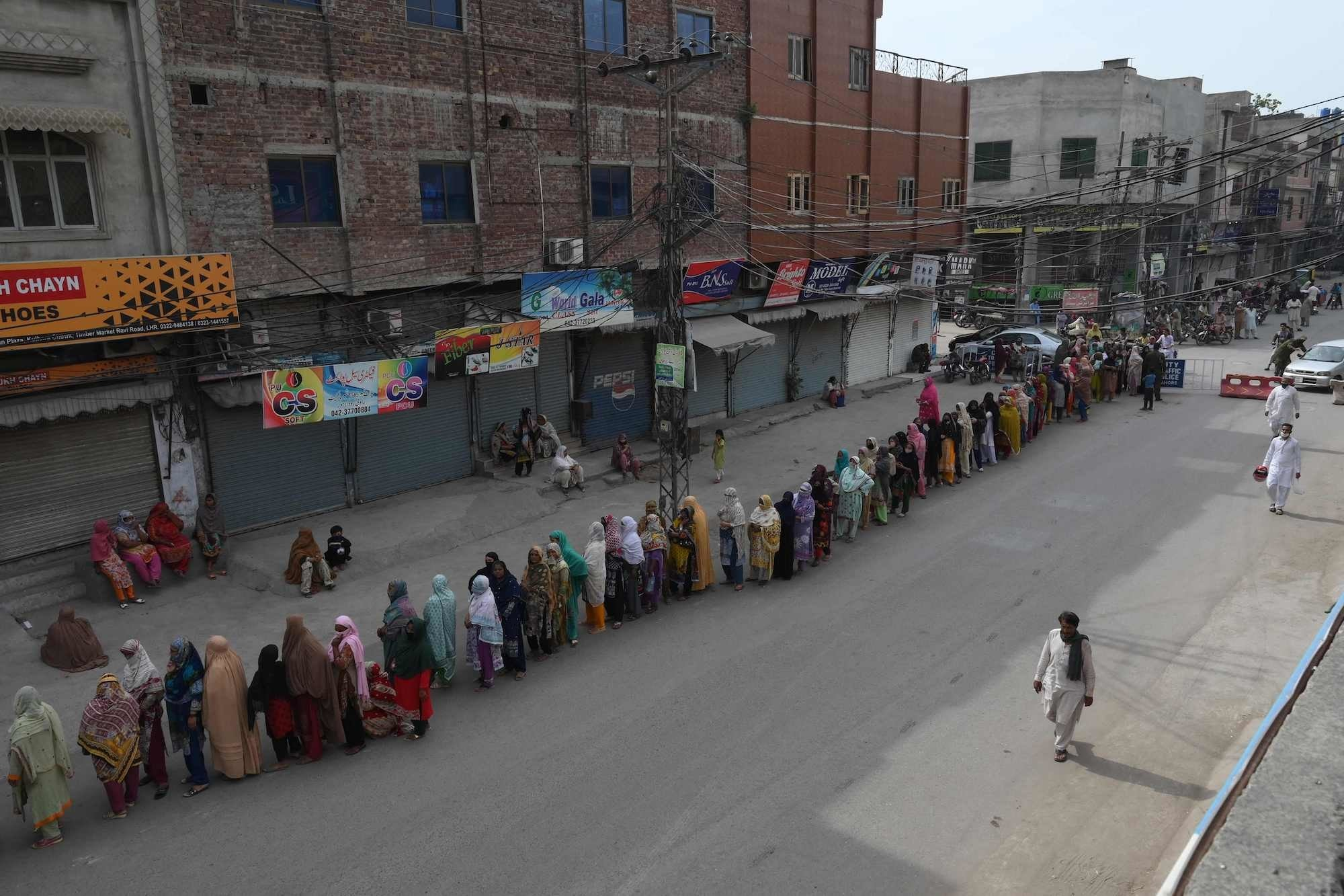 TOPSHOT - Women stand in a queue as they wait to collect cash of financial assistance through a mobile wallet under the governmental Ehsaas Emergency Cash Programme for families in need during a government-imposed nationwide lockdown as a preventive measure against the COVID-19 coronavirus, in Lahore on April 13, 2020. (Photo by ARIF ALI / AFP) — AFP or licensors