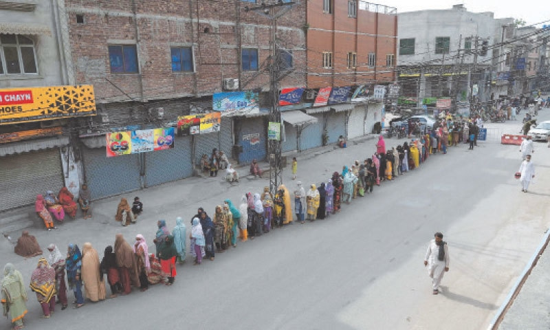 LAHORE: Women stand in a queue for collecting cash through a mobile wallet under the Ehsaas programme for families in need during the lockdown.—AFP