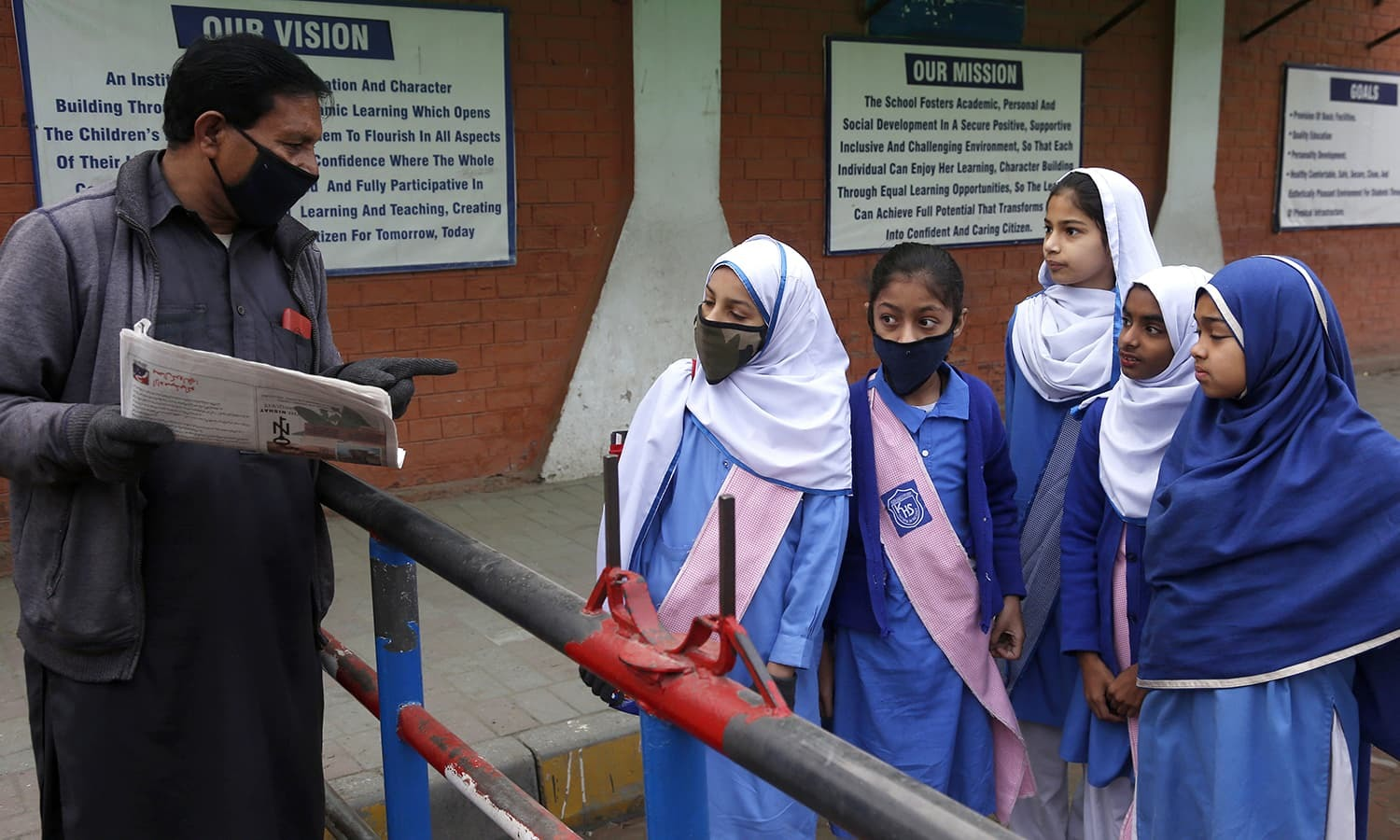 A security guard tells students that their school is closed by authorities to control possible spread of coronavirus, in Lahore, Pakistan, Saturday, March 14, 2020. For most people, the new coronavirus causes only mild or moderate symptoms. For some it can cause more severe illness. (AP Photo/K.M. Chaudary) — Copyright 2020 The Associated Press. All rights reserved.