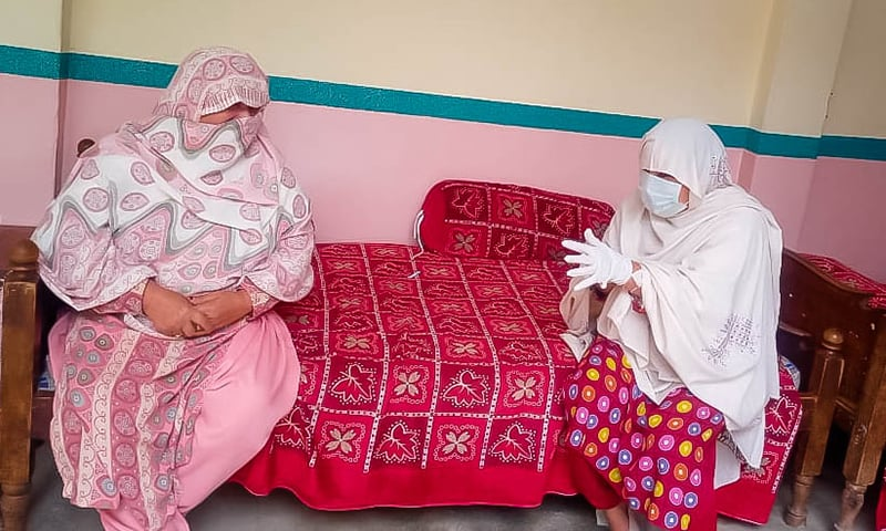 A healthcare worker shows preventive measures to a woman. — Photo by author