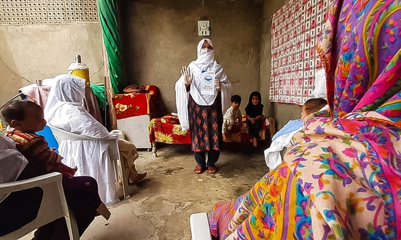 A lady health worker informs women about social distancing. — Photo by author