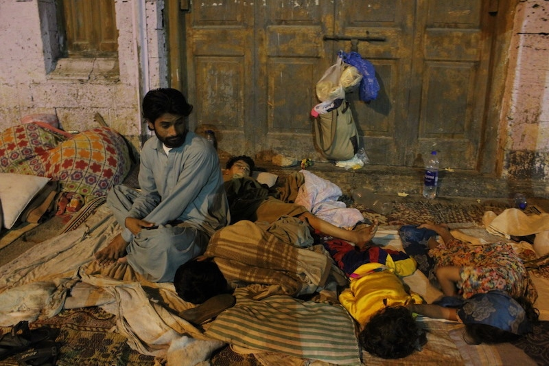 Shaukat Ai looks at his young cousins sleeping next to their mother, who is a patient at the SIUT and needs a dialysis procedure every week. The family has been living on the footpath for the past five years. — Photo by author