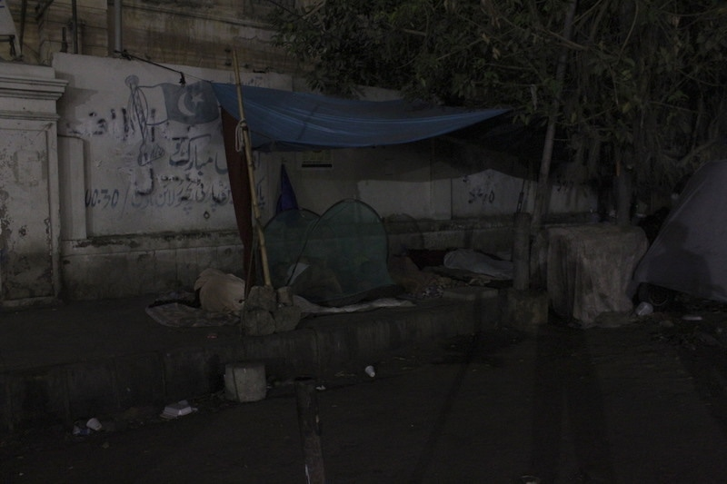 A man sleeps under a mosquito net on the footpath opposite the SIUT. — Photo by author