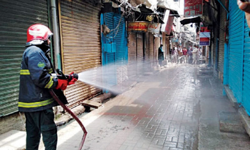 NAROWAL: The area where the cleric lived is being disinfected. — Dawn