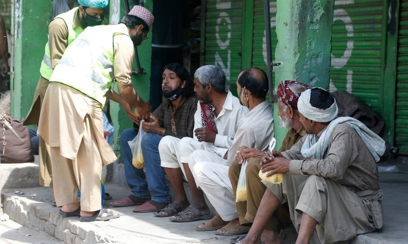 People offer food to daily wage workers in Lahore on April 15. — AP
