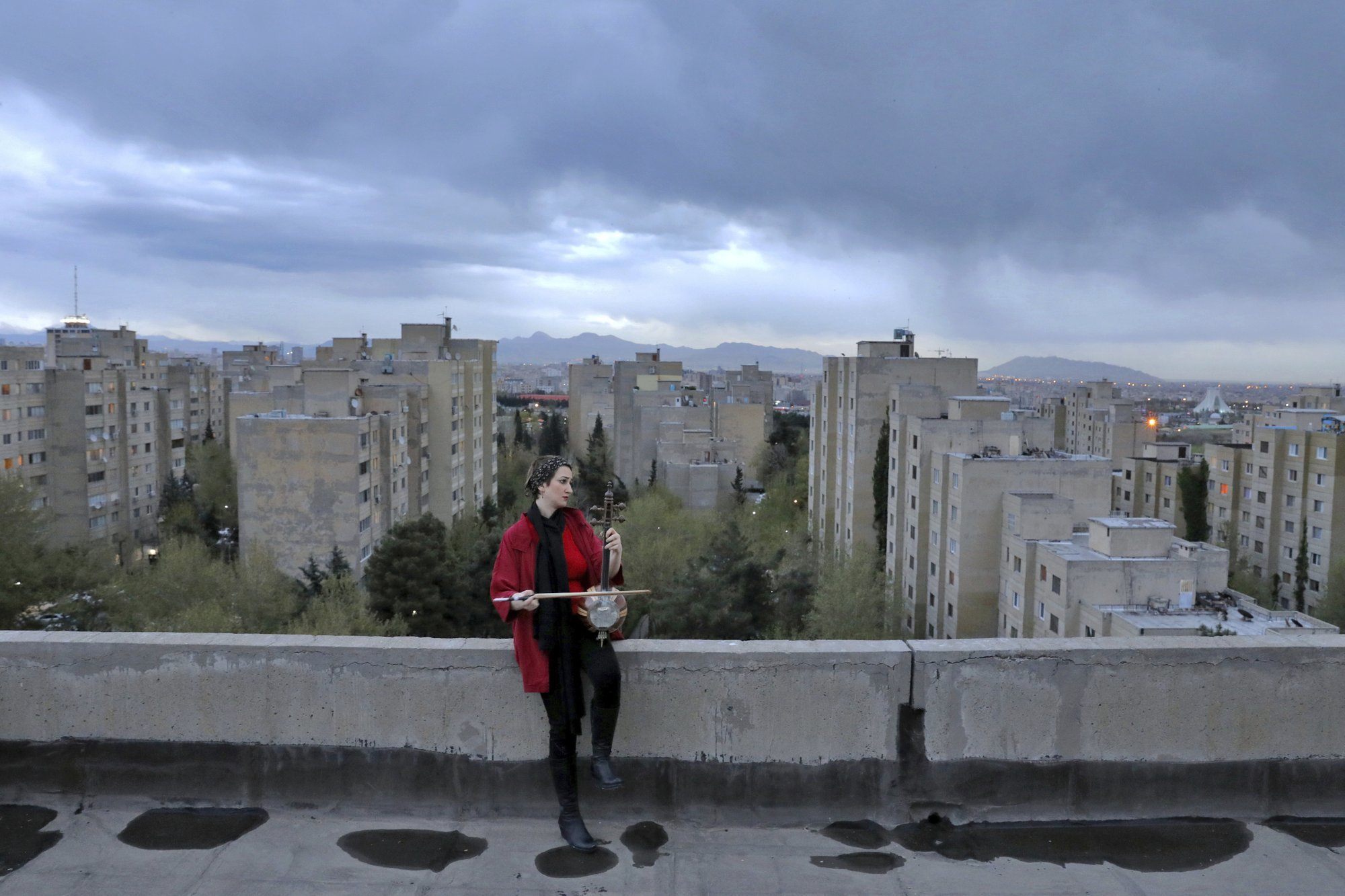 Musician Shiva Abedi, 30, plays kamancheh on the roof of her home during mandatory self-isolation due to the n during mandatory self-isolation due to the new coronavirus disease outbreak, in Tehran Iran. (AP Photo/Ebrahim Noroozi)