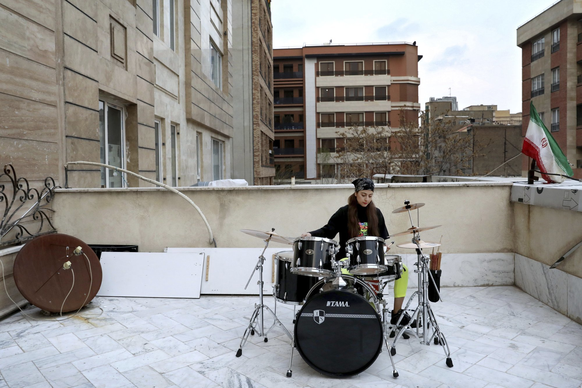 Farideh Sarsangi, 28, plays drums on the roof of her home during mandatory self-isolation due to the new coronavirus disease outbreak, in Tehran Iran. (AP Photo/Ebrahim Noroozi)